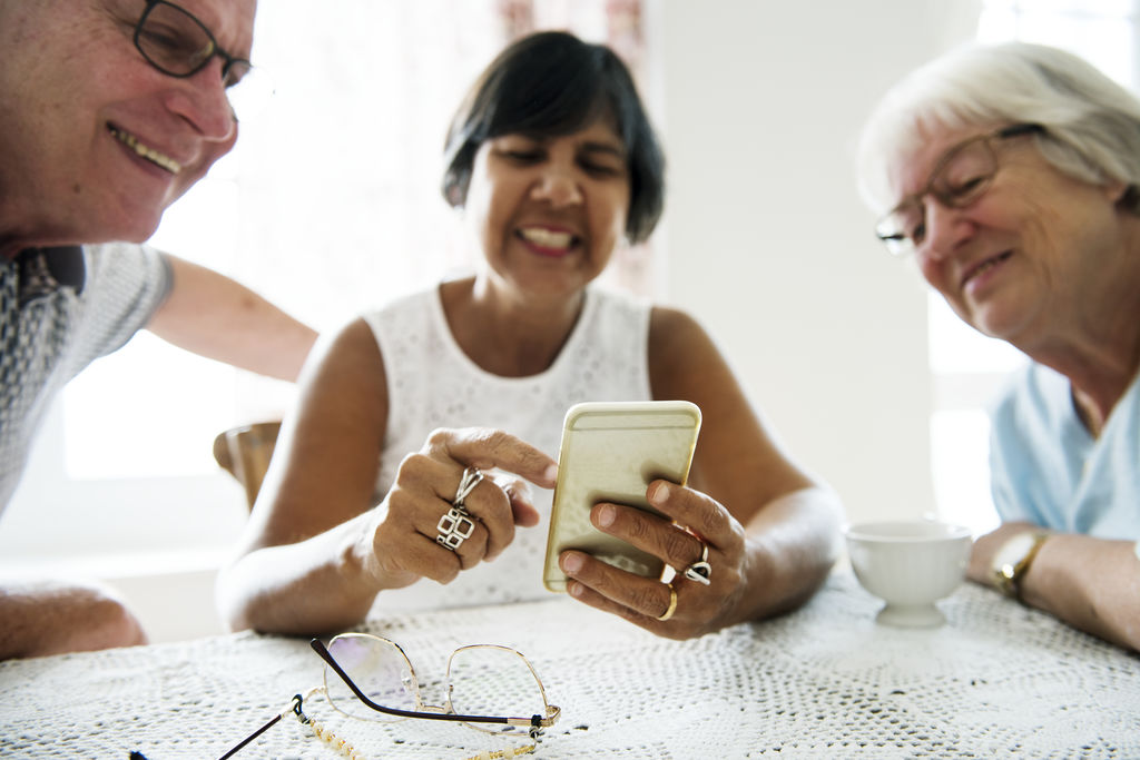 Group of diverse senior people using smartphone